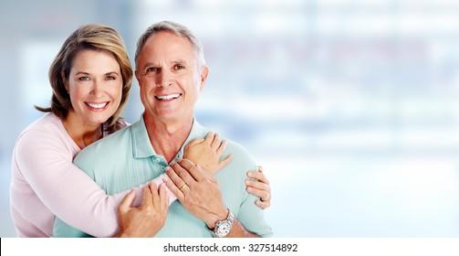 Happy senior couple portrait over blue background.