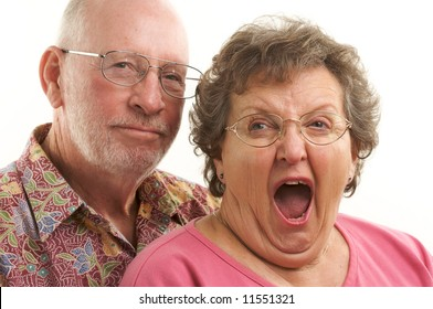 Happy Senior Couple poses for portrait as woman yawns.