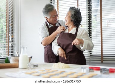 Happy Senior couple preparing the dough and baking cookies. Smiling Husband is tying apron for his wife.