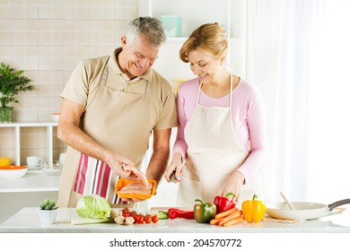 Happy Senior Couple preparing food in the kitchen.