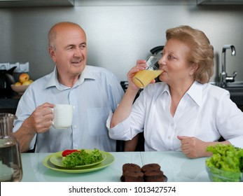 Happy senior couple preparing healthy vegetarian breakfast with fruits and vegetables - Old cheerful people taking care about nutrition - Health,vegan and bio concept .