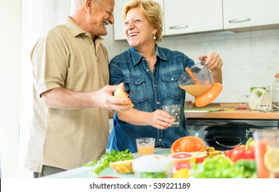 Happy senior couple preparing healthy vegetarian breakfast with fruits and vegetables - Old cheerful people taking care about nutrition - Health,vegan and bio concept - Focus on woman - Warm filter