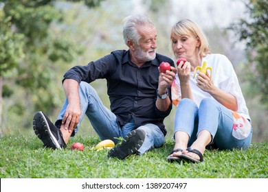 Happy senior couple relaxing in park eating apple an banana together morning time. old people sitting on grass in the autumn park . Elderly resting .mature relationships. family