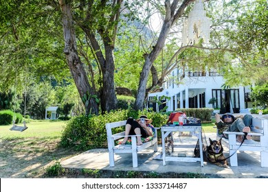 Happy senior couple relaxing with a pet dog in the garden