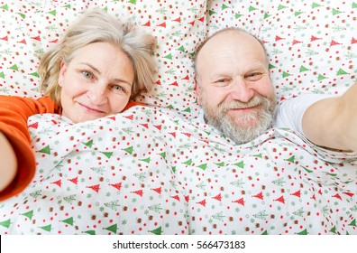 Happy senior couple resting in the bed
