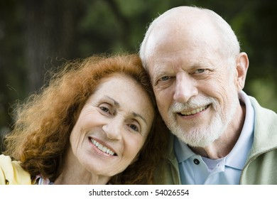 Happy Senior Couple Resting Heads on Each Other Outdoors in a Park