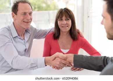 Happy senior couple shaking hands with realtor