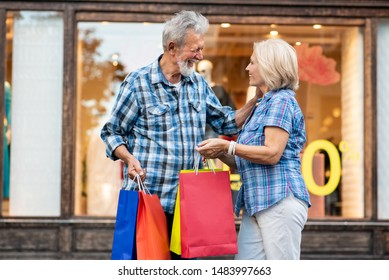 Happy senior couple with shopping bags