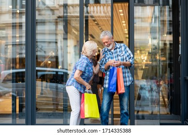 Happy senior couple with shopping bags in front of shopping window