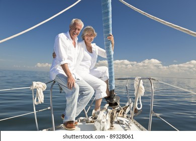 A happy senior couple sitting at the bow of a sail boat on a calm blue sea