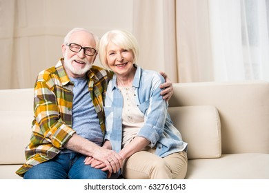 Happy senior couple sitting embracing on sofa and smiling at camera