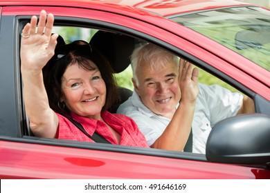 Happy Senior Couple Sitting Inside Car Waving Goodbye