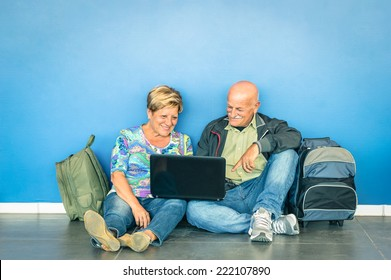 Happy senior couple sitting on floor with laptop waiting for flight at airport - Concept of active elderly and interaction with new technologies - Travel lifestyle without age limitation - Cyan filter