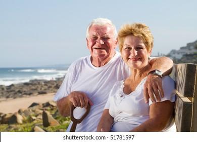 happy senior couple sitting on beach bench