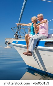 A happy senior couple sitting on the side of a sail boat on a calm blue sea, the woman is pointing to the horizon