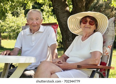 Happy senior couple sitting at the round table in the garden and enjoying life. Concept of active elderly people during retirement. Everyday joy lifestyle without age limitation.