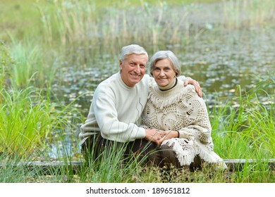 Happy senior couple sitting in summer near lake