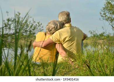 Happy senior couple sitting in summer near lake