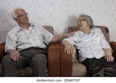 Happy senior couple sitting in their house and talking