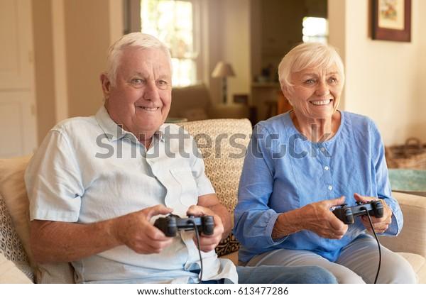 Happy Seniorenpaar sitzen zusammen auf ihrem Wohnzimmersofa und halten Controller und lachen beim Spielen eines Videospiels