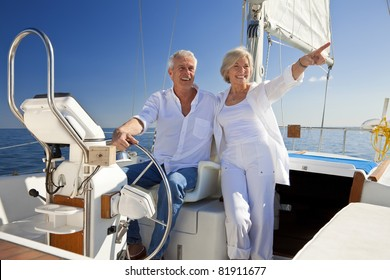 A happy senior couple sitting at the wheel of a sail boat on a calm blue sea