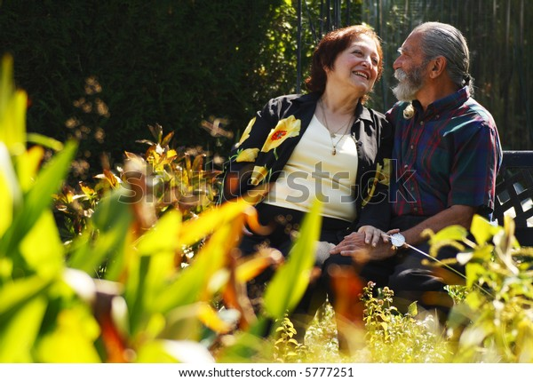 Happy Senior Couple smiling and looking at each other in the park outdoors.