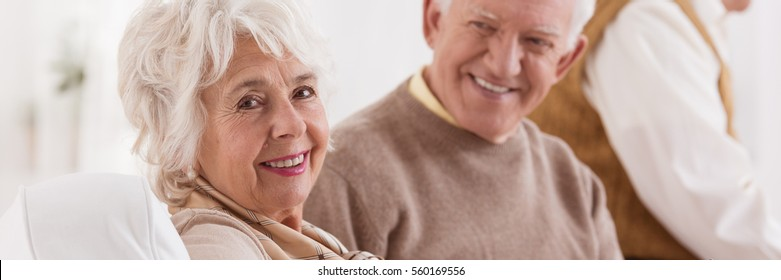 Happy senior couple smiling and sitting on a sofa