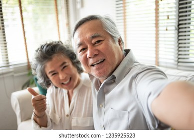Happy Senior Couple smiling and taking selfie photos with smartphone together at their home.