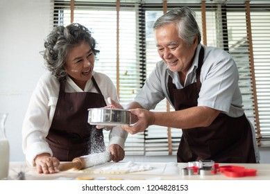 Happy Senior Couple sprinkling the fresh dough with white flour in the kitchen. Asian Lover Preparing bakery together.