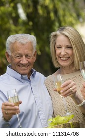 Happy senior couple standing together while holding glass of champagne