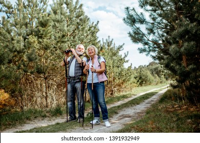 Happy senior couple standing together with binoculars, backpacks and trekking sticks while hiking in the forest. Concept of an active lifestyle on retirement