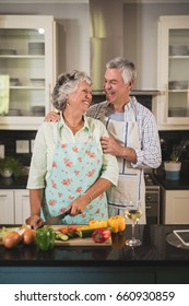Happy senior couple standing together in kitchen at home
