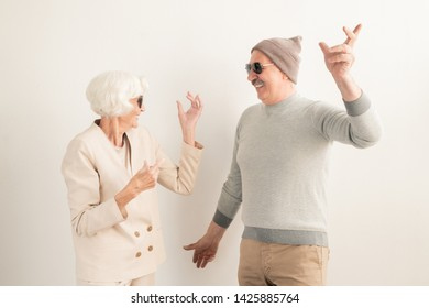 Happy senior couple in sunglasses and casualwear enjoying leisure while dancing over white background in studio