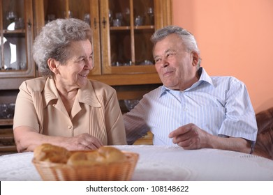 Happy senior couple at the table indoors
