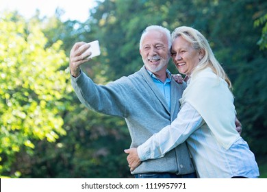 Happy senior couple taking a selfie, outdoors