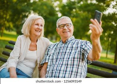 Happy senior couple is taking selfie in park.