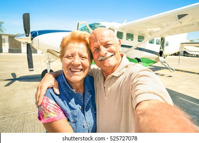 Happy senior couple taking selfie with private ultralight plane at tour around world - Elderly concept with active retired people enjoying pension moments - Warm bright sunny afternoon color tones