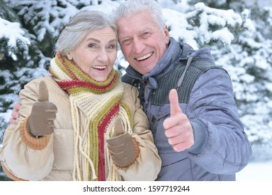 Happy senior couple with thumbs up at snowy winter park