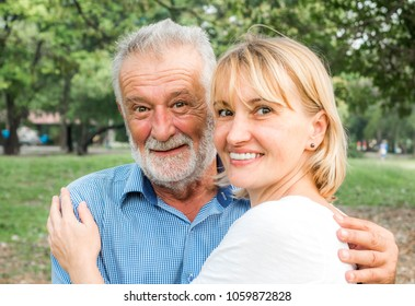 Happy senior couple together in a summer park, Being together and staying strong, happy life.