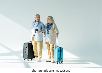 happy senior couple with traveling bags, passports and tickets, traveling concept