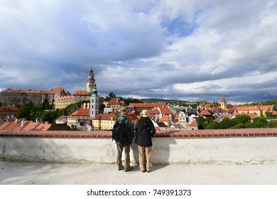 A happy senior couple traveling together admiring the view of Cesky Krumlov, Czech republic. Active lifestyle concept.