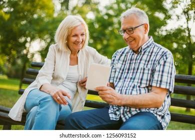 Happy senior couple is using digital tablet in park.