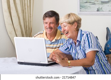 happy senior couple using laptop computer in living room