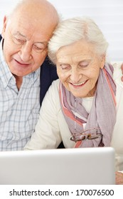 Happy senior couple using social media with laptop computer
