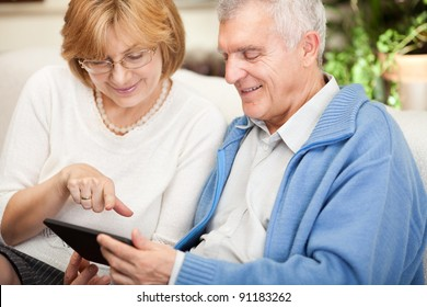 Happy senior couple using tablet PC at home