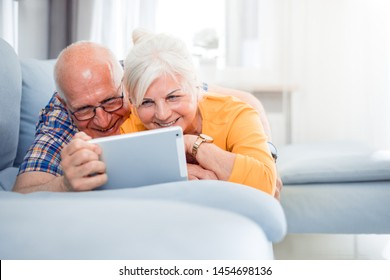 Happy senior couple video chatting using tablet at home