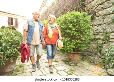 Happy senior couple walking holding hand in San Marino old town castle - Active elderly and travel lifestyle concept with retired mature people at Italy roadtrip - Sunshine halo with sunflare filter