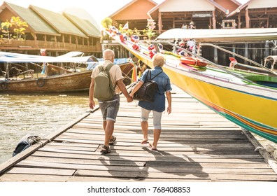 Happy senior couple walking holding hand at Koh Panyi muslim floating village - Active elderly and travel lifestyle concept with retired mature people at Phang Nga bay Thailand - Warm day filter