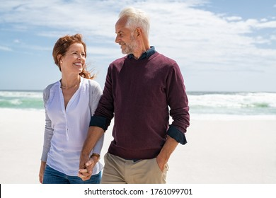 Happy senior couple walking on the beach in a sunny day. Smiling mature couple looking at each other on beach during sunset with copy space. Retired man in love with his wife relaxing during vacation.