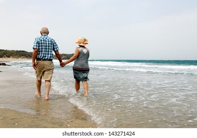 Happy senior couple walking together on a beach